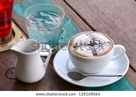 Cup of coffee with artistic cream decoration - stock photo
