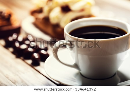 Cup of coffee with assorted desserts in the background