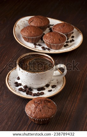 Cup of coffee with beans  and  chocolate muffins