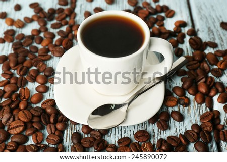 Cup of coffee with beans on color rustic wooden background - stock photo