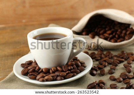 Cup of coffee with beans on rustic wooden background - stock photo