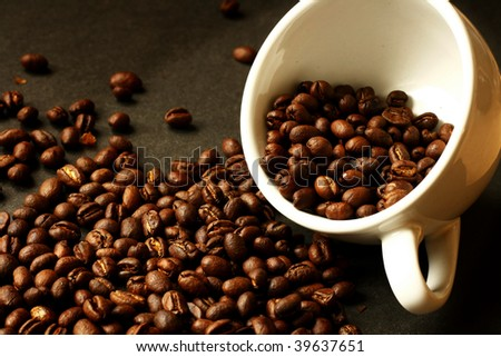 Cup of coffee with beans spilling onto the ground. - stock photo