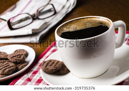 Cup of coffee with biscuits, glasses, news on a wooden background