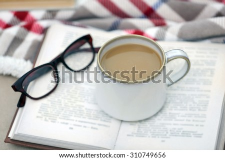Cup of coffee with book on sofa in living room