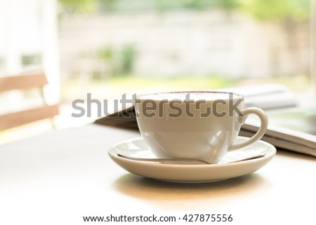 Cup of coffee with books on the table , garden view