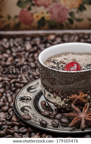 Cup of coffee with cherry, anise  and coffee beans against flower painted background  - stock photo