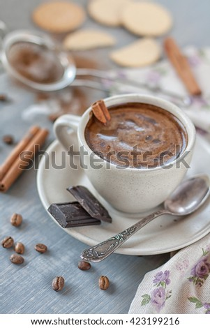 Cup of coffee with cinnamon and chocolate chips on saucer - stock photo