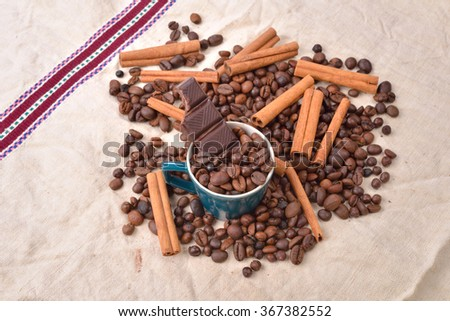 Cup of coffee with cinnamon sticks, bitten bar of chocolate on vintage texture. Roasted coffee beans on jute background. Morning pleasures. Selective focus - stock photo