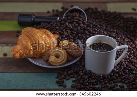 Cup of coffee with cookies and beans on grunge wooden floor - stock photo