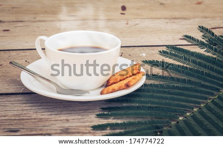 Cup of coffee with crackers on wooden