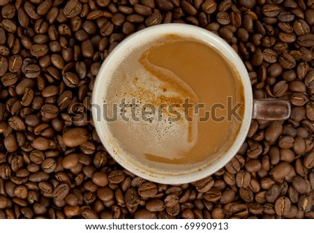 Cup of coffee with cream and coffee beans on background. See more my photos of cups: http://www.shutterstock.com/sets/66603-cups.html?rid=522649 - stock photo