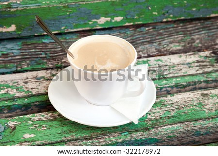 Cup of coffee with cream is on old wooden bench in autumn park.  Selective focus with shallow DOF - stock photo