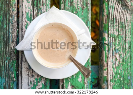 Cup of coffee with cream is on old wooden bench in autumn park.  Top view, selective focus - stock photo