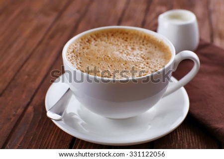 Cup of coffee with cream on brown napkin