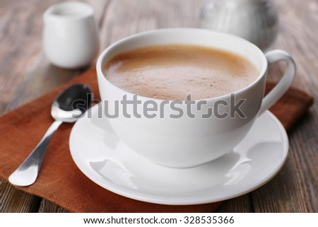 Cup of coffee with cream on brown napkin closeup