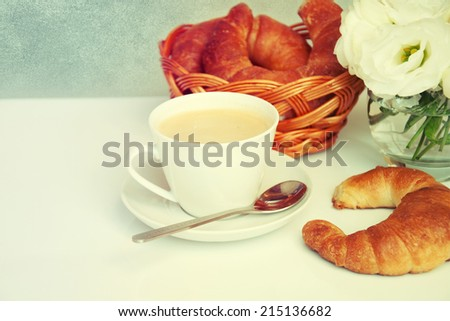 Cup of coffee with croissants and bouquet of flowers.