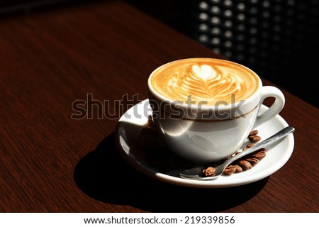 Cup of coffee with cute drawing in cafe - stock photo