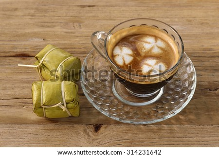 Cup of coffee with dessert on wooden background
