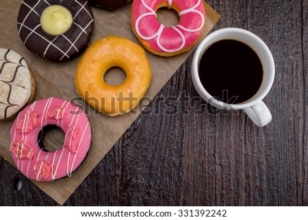 Cup of coffee with donut on wooden desk. Top view - stock photo
