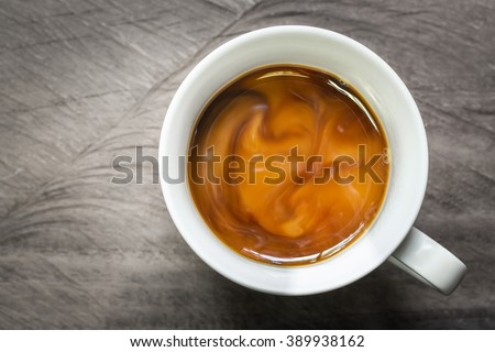 Cup of coffee with flowing milk on wooden background - stock photo