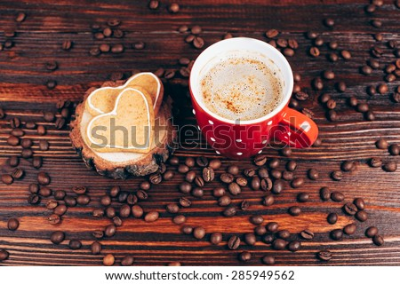 Cup of coffee with foam, heart shaped cookies and coffee beans, lying on the wooden stand, on wooden table - stock photo
