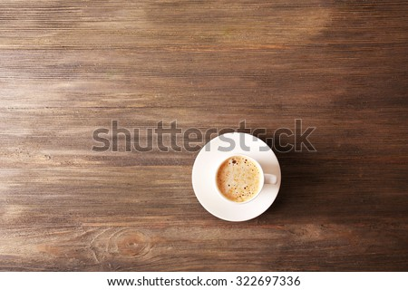 Cup of coffee with foam on wooden table, top view - stock photo