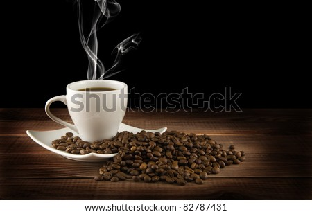 cup of coffee with grains on a black background - stock photo