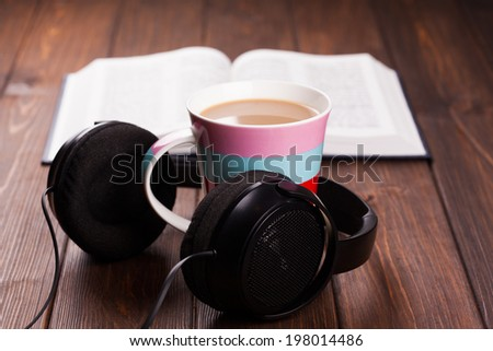 cup of coffee with headphones on wooden background  - stock photo