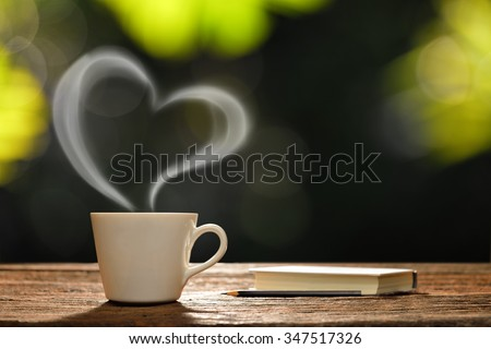 Cup of coffee with heart-shaped smoke and book in the garden - stock photo