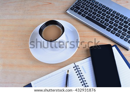 Cup of Coffee with keyboard and mouse, fountain pen, notebook, calculator and smartphone on a table
