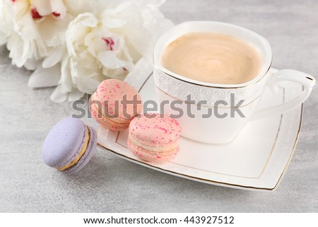 Cup of coffee with macaroons and peonies on wooden table