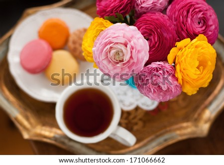 Cup of coffee with macaroons on a table with flowers ranunculus - stock photo