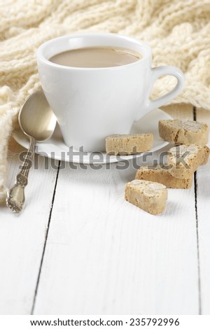 Cup of coffee with milk, almond cookies and warm woolen knitwear. - stock photo