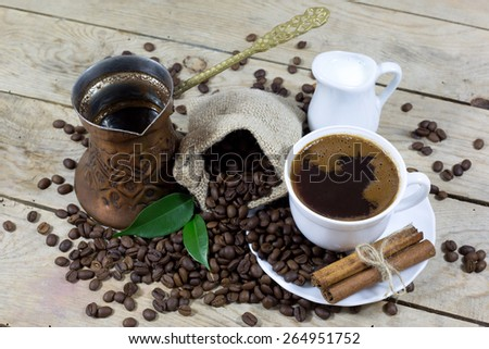 Cup of Coffee with Milk and Coffee Beans on an Old Wooden Table, View From the Top - stock photo