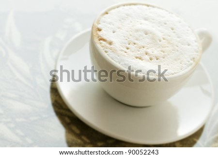 Cup of coffee with milk foam in white cup with saucer