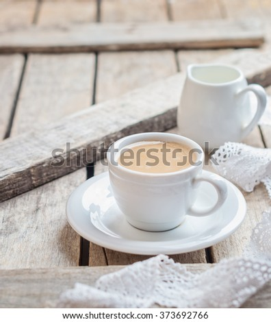 cup of coffee with milk on a light wooden background