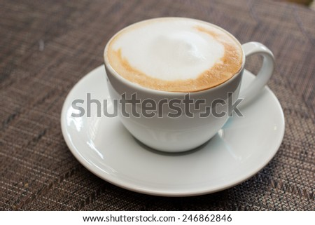 cup of coffee with milk on table , in cafe.