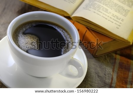 Cup of coffee with old books in the background - stock photo