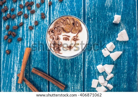 Cup of coffee with picture of woman face on the table with a coffee beans and sugar - stock photo
