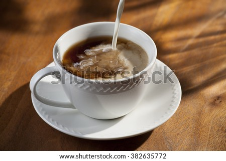 Cup of Coffee with Pouring Creamer - stock photo