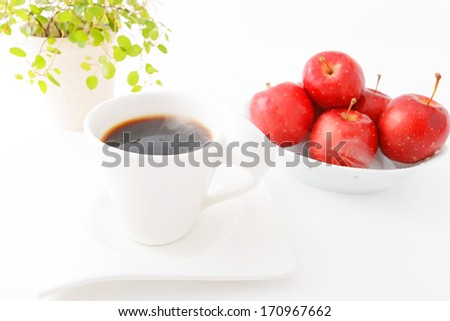 Cup of coffee with ripe red apples