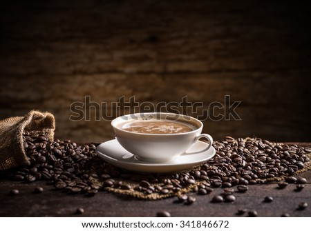 Cup of coffee with scattered coffee beans on wooden background
