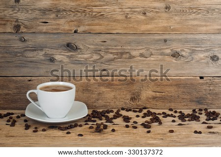 cup of coffee with scattered coffee grains are on the wood background - stock photo