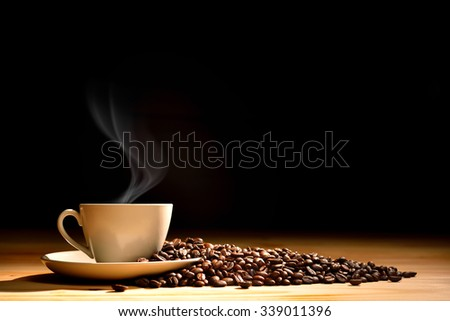 Cup of coffee with smoke and coffee beans on old wooden background - stock photo