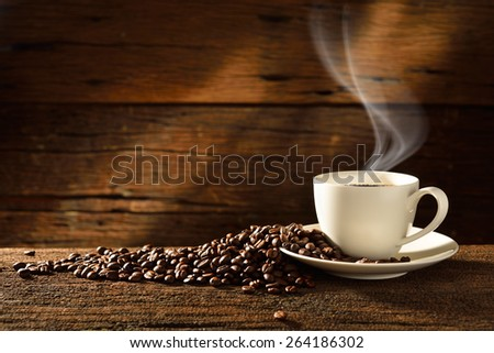 Cup of coffee with smoke and coffee beans on old wooden background,This photo is available without smoke - stock photo