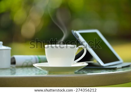Cup of coffee with smoke and tablet computer in garden - stock photo