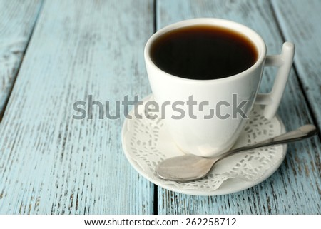 Cup of coffee with spoon on color rustic wooden background - stock photo