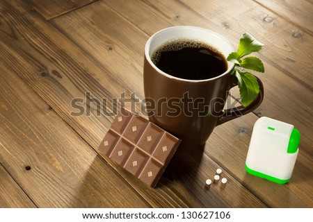 Cup of coffee with stevia sweetener tablets and Belgian chocolate without sugar - stock photo