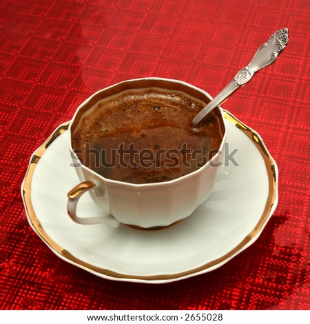 Cup of coffee with the spoon on a red background - stock photo