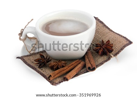 cup of coffee with three cinnamon sticks and star anise on a sackcloth, isolated on a white background - stock photo